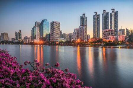 Lake with Purple Flowers in City Park under Skyscrapers at Sunrise. Benjakiti Park in Bangkok, Thailand Stockfoto