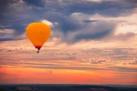 Ballon à air chaud volant avec un beau ciel dramatique coloré au coucher du soleil