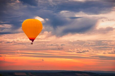 Mongolfiera che vola con un bellissimo cielo drammatico colorato al tramonto
