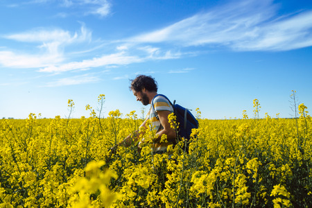 Young caucasian man walking through field of rapeseed Imagens