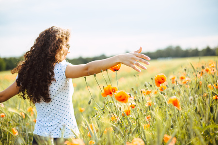 young curly carefree woman running through a field of wildflowers on a summer day
