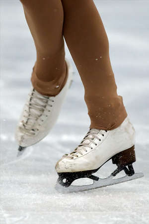Professional worn figure skates close-up on the ice making a rotation  white ice skates on the ice