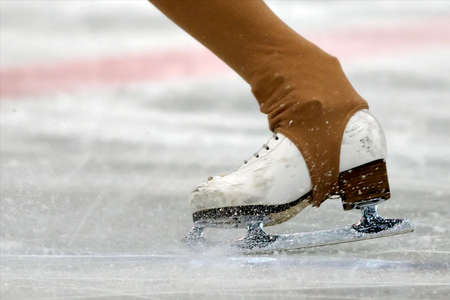 Professional worn figure skates close-up on the ice skating backwards  white ice skates on the ice photo