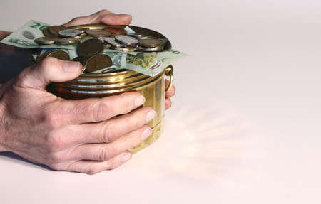 retained: Dinero en olla de oro con manos reteni�ndolo Foto de archivo