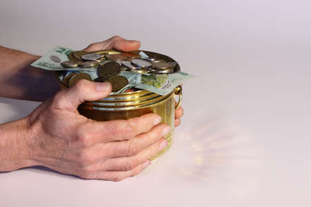 covetous: Money in pot of gold with hands holding it Stock Photo