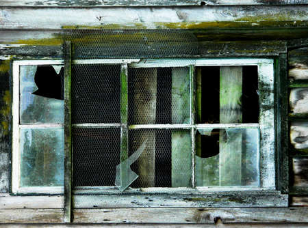 Broken windows of old barn with peeling paint photo