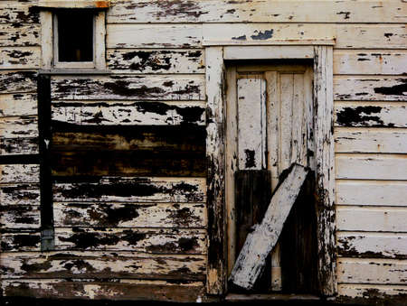 Door and window of old house with peeling paint