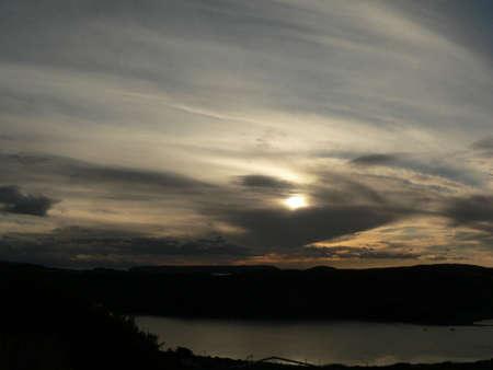 Sun reflecting through cloud over water scene