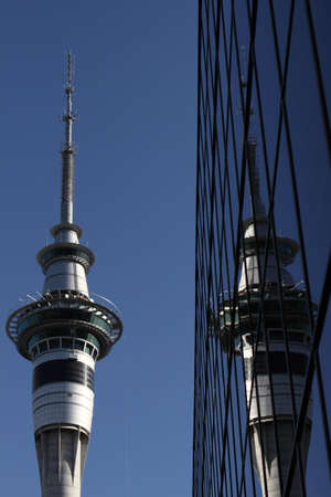 Skytower building reflecting in glass sided corporate building Auckland New Zealand