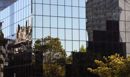 Trees and other building reflecting in glass sided corporate building Standard-Bild