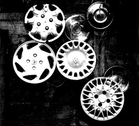 hubcap: Collection of old hubcaps mounted on a wall