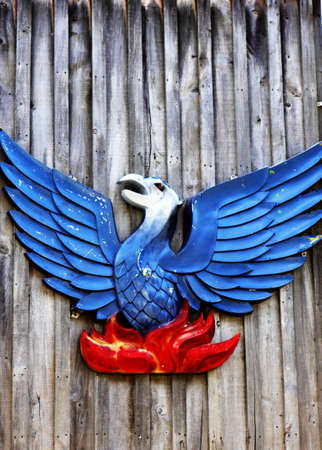 Red and blue stylised bird symbol hanging on fence