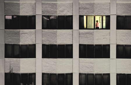 Single lit window with woman standing in it in a dark building