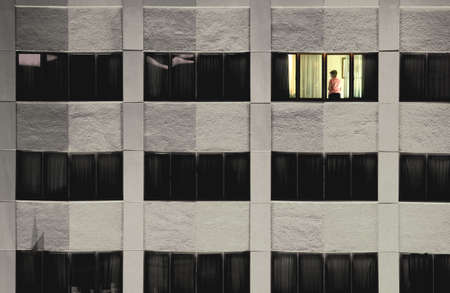 Single lit window with woman standing in it in a dark building photo