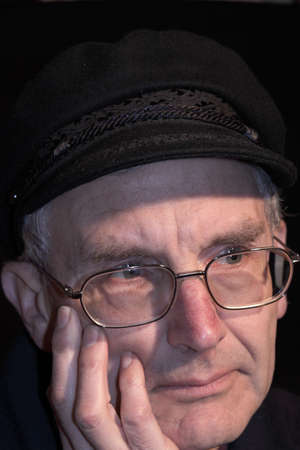 Older person thinking, with hat on photo