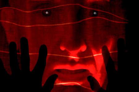 Hands up in horror at face through curtain Standard-Bild