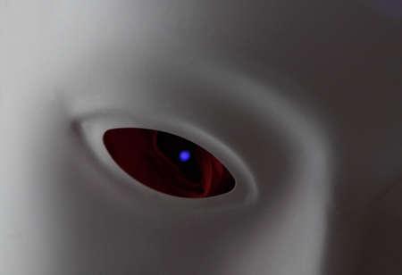 Alien eye staring through white mask