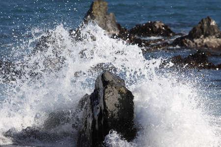 Wave breaking over rocks at rocky sea shore Standard-Bild