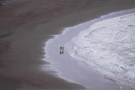 Two people walking along sea shore, following curved shoreline