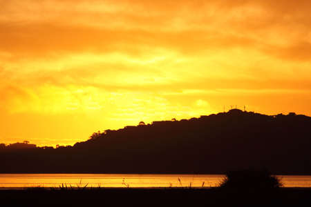 Intense yellow and orange sunset over water, with hill in background