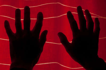 Silhouetted hands held up in fright, against a red curtain background with white wavy lines, suggesting tension Standard-Bild