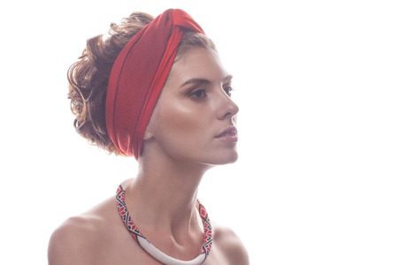 turban: Portrait of a girl with beaded ornaments in red turban on a white background