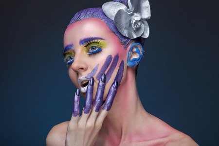 eyelids: Portrait of a woman with creative make-up on a blue background. With bright colors on her hair and face. Art beauty. With painted the fingers Stock Photo