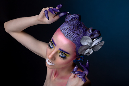 eyelids: Creative portrait of woman with art make-up. With raised hands and on a blue background