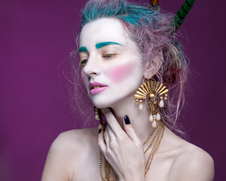 eyelids: Creative portrait of young woman with artistic make-up. With bright colors in her hair and a white face.
