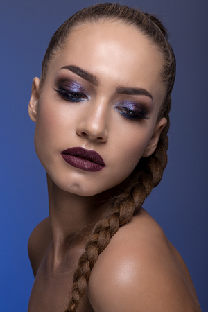 Portrait of a teenage girl with a creative make-up, beautiful oblique and plump lips. On a blue background. Stock Photo