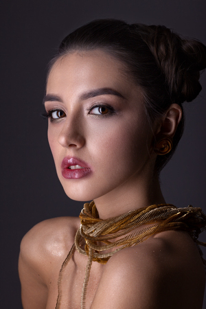 Portrait of a beautiful girl with a creative hairstyle and makeup on a gray background. With a necklace of bronze knocks on his neck.