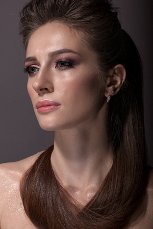 Portrait of a beautiful woman on a dark background, with a beautiful make-up and hairstyle