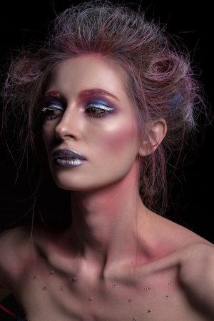 Portrait of a beautiful woman with creative hair and makeup on a black background. Artistic image.
