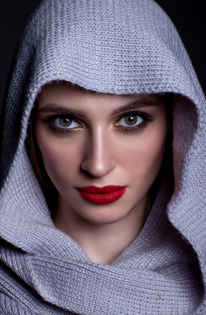 Portrait of a beautiful woman on a black background with a knitted scarf on her head, beautiful make-up and with red lipstick. Stock Photo