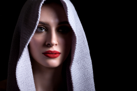 Portrait of a beautiful woman on a black background with a knitted scarf on her head, beautiful make-up and with red lipstick. 스톡 콘텐츠