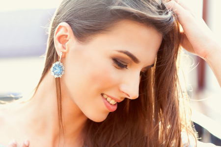Portrait of a beautiful woman in sunny weather. In the youth style, beautiful hair and make-up. Stock Photo