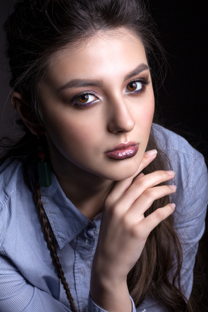Portrait of a beautiful teen girl on a black background. With beautiful makeup and piercing eyes.
