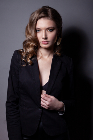 Portrait of a beautiful woman in a black jacket. With beautiful hair and makeup on a gray background.