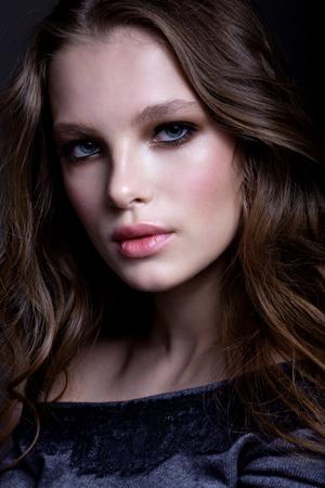 Portret van een mooi tienermeisje, met een mooie make-up en kapsel op een grijze achtergrond.