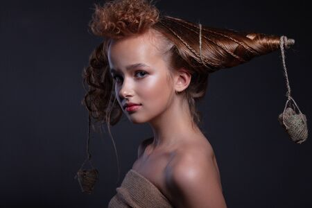 Portrait of a beautiful teenager girl with creative hairstyle and beautiful make-up on a dark background.