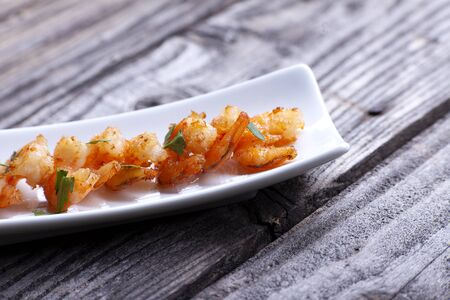 Fried prawns in a black plate on gray boards.