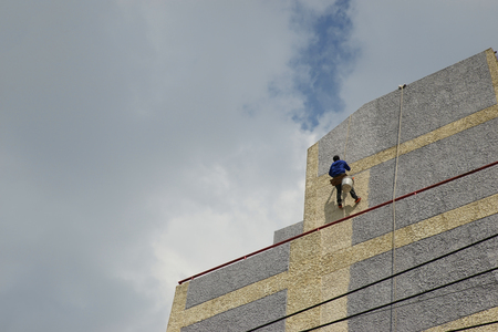risky: A man is risky painting high wall. Stock Photo