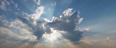 Sun as bursting through clouds in a blue sky. photo