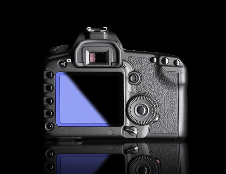 Professional Digital Camera, back view. It is isolated on black background with reflection photo