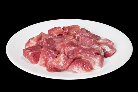 Pieces of raw meat on a white plate is isolated on a black background photo