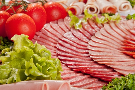 salami: Cutting sausage and cured meat with a parsley Stock Photo
