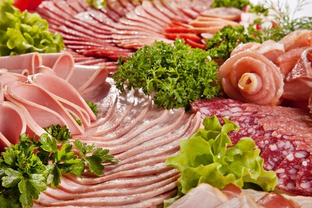 cured: Cutting sausage and cured meat with a parsley Stock Photo