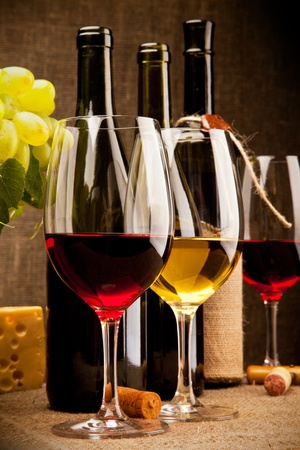 wine and grapes: Still life with wine bottles, glasses, grapes and cheese  Stock Photo