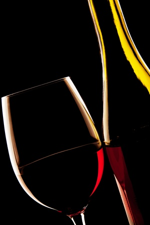 Backlit detail of a glass of red wine and the wine bottle against a solid black background.