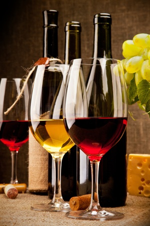 Still life with wine bottles, glasses, grapes and cheese  Stock Photo
